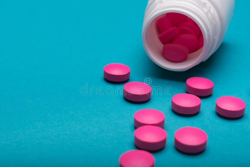 A garrafa da medicamentação e os comprimidos cor-de-rosa brilhantes derramaram na obscuridade - fundo colorido azul Comprimidos d fotos de stock