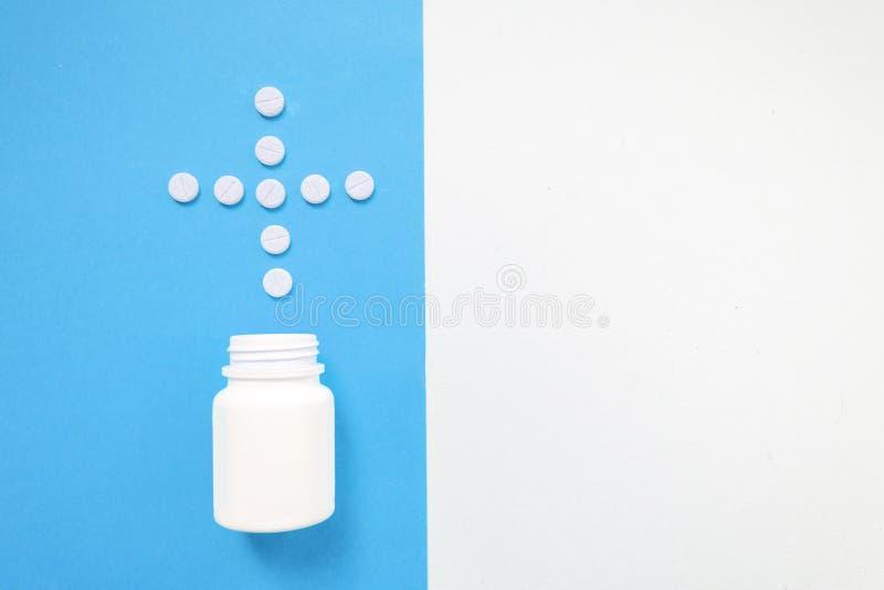 A garrafa da medicamenta??o e os comprimidos brancos derramados na cor pastel azul coloriram o fundo Medicamenta??o e fundo da co fotos de stock