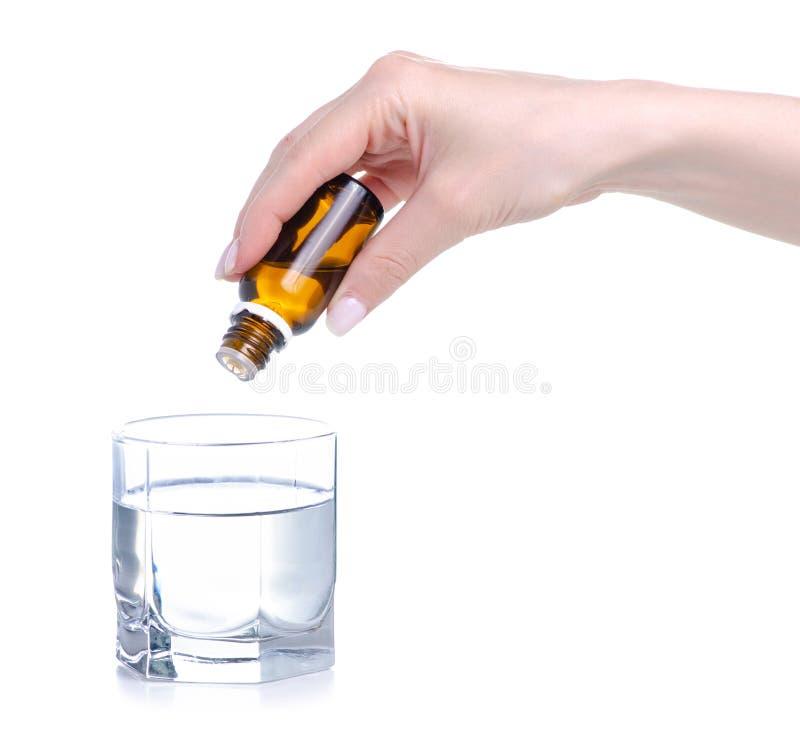 A garrafa da medicina goteja ? disposi??o em um vidro da ?gua imagem de stock royalty free