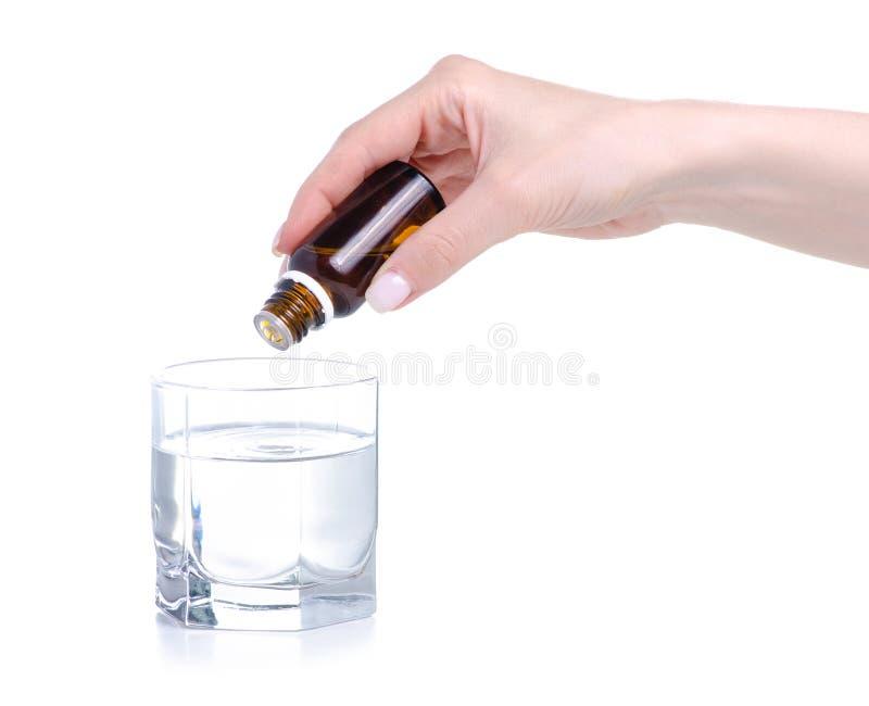 A garrafa da medicina goteja ? disposi??o em um vidro da ?gua imagens de stock royalty free