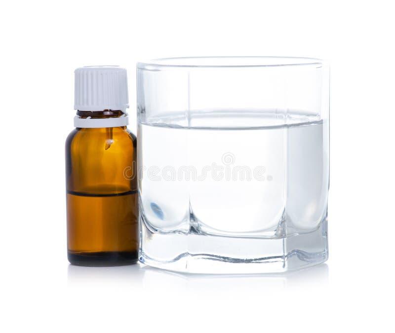 A garrafa da medicina goteja em um vidro da ?gua imagem de stock