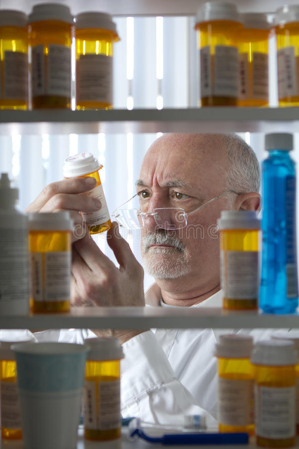 Garrafa da prescrição da leitura do homem superior fotografia de stock