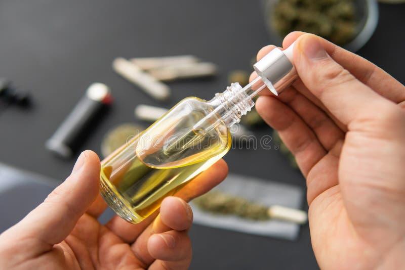 Garrafa da terra arrendada da m?o do ?leo do cannabis na pipeta, erva natural, fim acima, conceito m?dico da marijuana fotos de stock royalty free