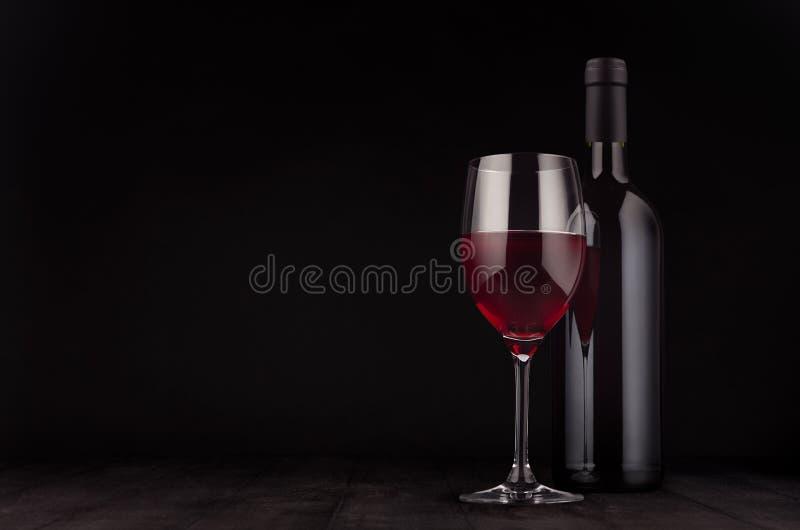 Garrafa da zombaria do vidro do vinho tinto e de vinho acima no fundo de madeira elegante do preto escuro, espaço da cópia foto de stock