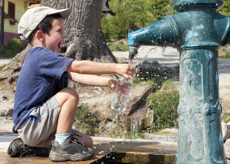 Garrafa de água de enchimento da criança imagens de stock
