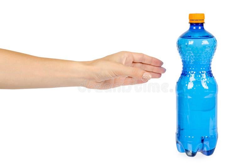 Garrafa de água plástica azul com o tampão alaranjado, isolado no fundo branco, com mão fotografia de stock royalty free