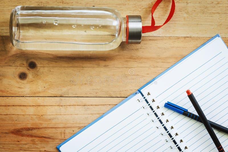 Garrafa de água, um caderno aberto e penas no backgr de madeira da tabela imagem de stock