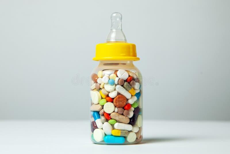 Garrafa de alimentação do bebê enchida com os comprimidos Com leite de mãe, a criança obtém tudo que a mãe come closeup foto de stock