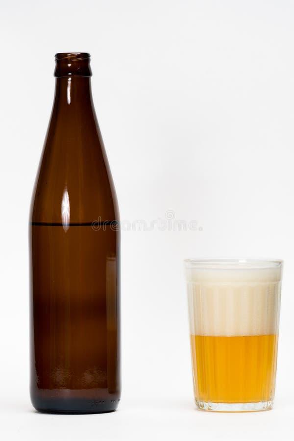 Garrafa de cerveja aberta e meio vidro foto de stock