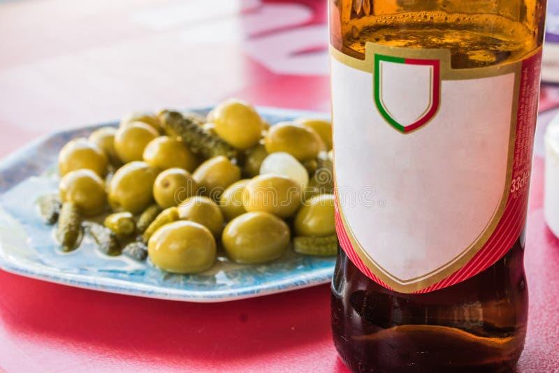 Garrafa de cerveja com a placa das azeitonas fotografia de stock