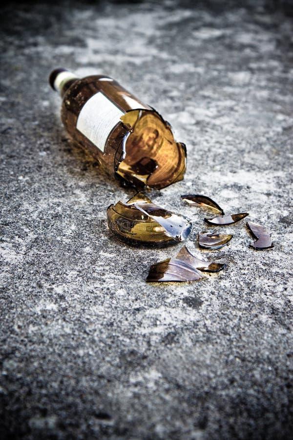 Garrafa de cerveja marrom quebrada que descansa na terra: conceito do alcoolismo imagens de stock royalty free