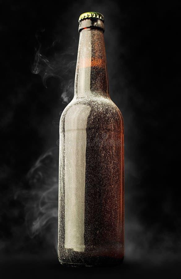 Garrafa de cerveja na geada com vapor imagens de stock