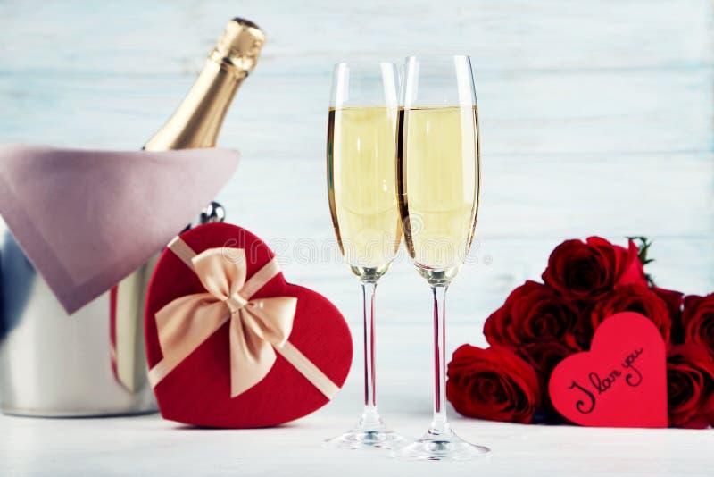 Garrafa de Champagne com caixa de presente e rosas imagem de stock