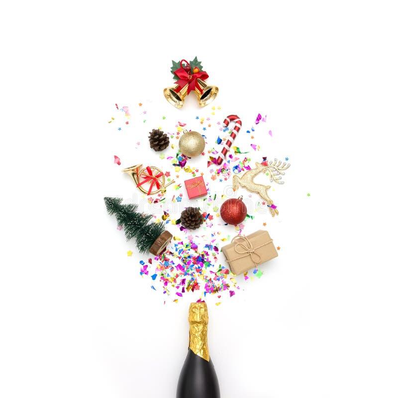 Garrafa de Champagne com confetes do vário partido e decoração do Natal em um fundo branco foto de stock