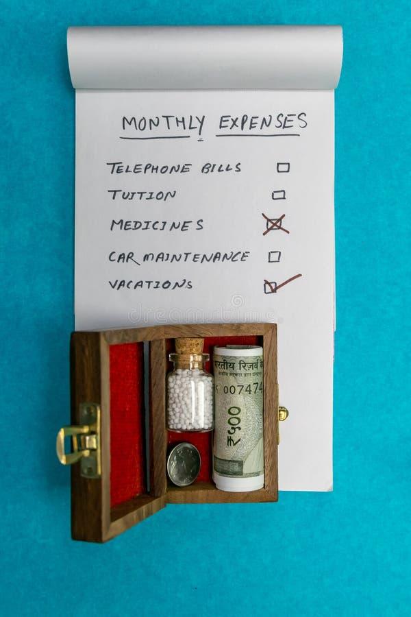 Garrafa de comprimidos homeopaticamente e da moeda indiana na caixa de madeira e no bloco de notas velhos no fundo azul - conceit fotografia de stock royalty free
