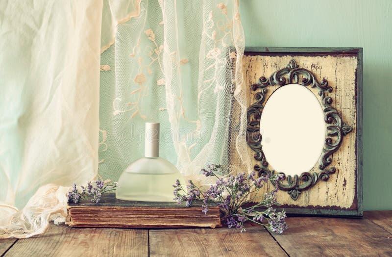 Garrafa de perfume fresca do vintage ao lado das flores aromáticas e quadro vazio antigo na tabela de madeira imagem filtrada ret foto de stock royalty free
