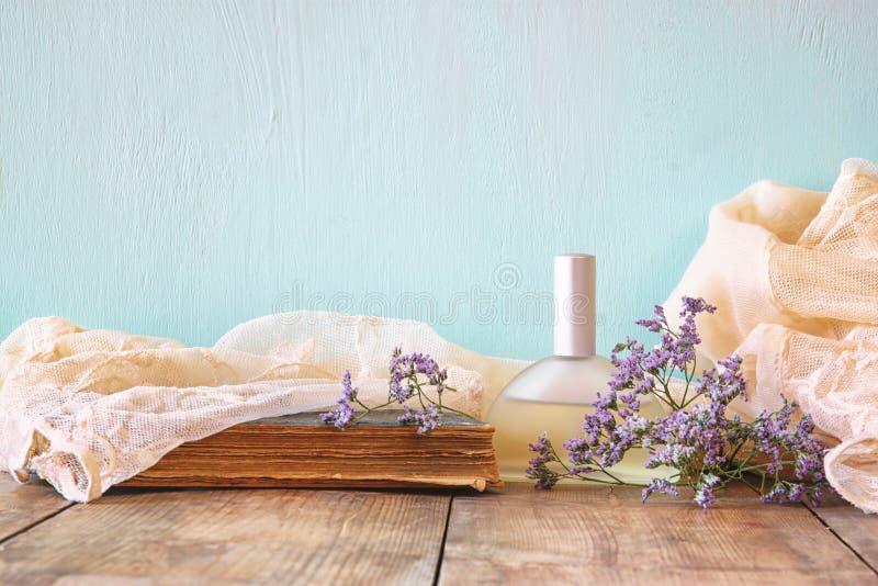 Garrafa de perfume fresca do vintage ao lado das flores aromáticas na tabela de madeira imagem filtrada retro imagem de stock royalty free