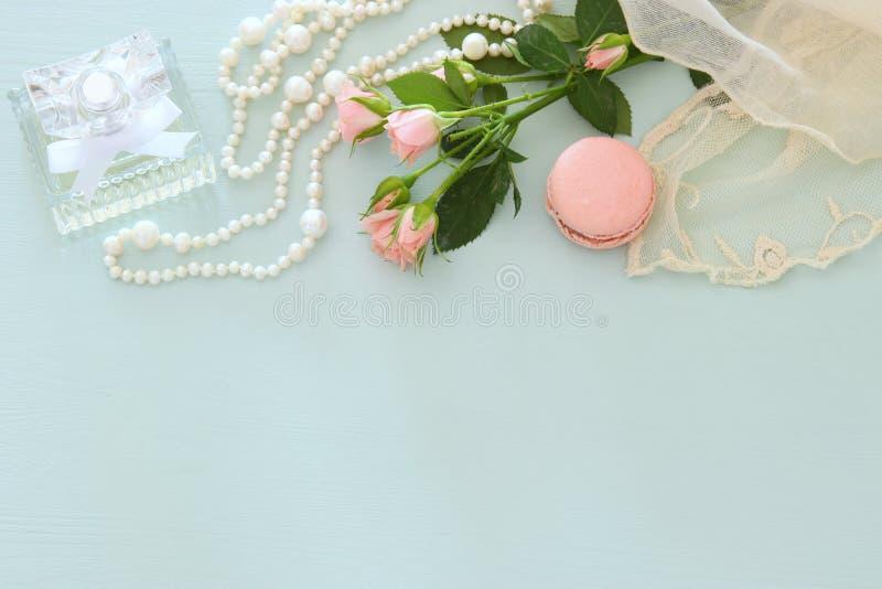 Garrafa de perfume fresca do vintage ao lado das flores aromáticas na tabela de madeira imagens de stock