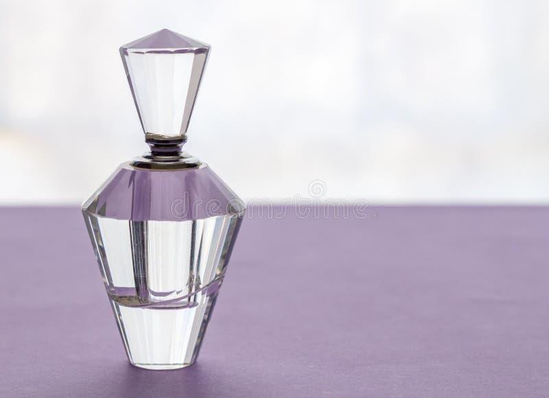 Garrafa de perfume vazia do cristal do vintage com o bujão no lilás fotografia de stock