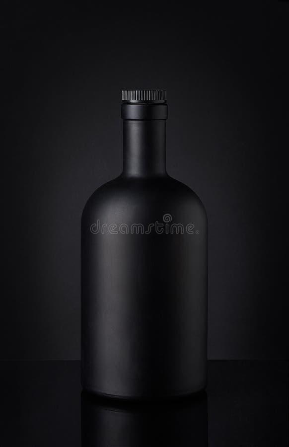 Garrafa de uísque preta no fundo escuro foto de stock