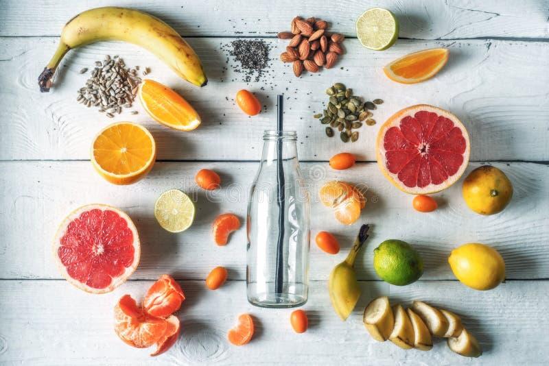 Garrafa de vidro cercada por frutos e por porcas diferentes na opinião de tampo da mesa de madeira branca fotos de stock