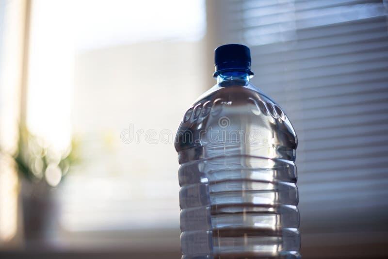 Garrafa de vidro com água na tabela o fundo da janela imagens de stock royalty free