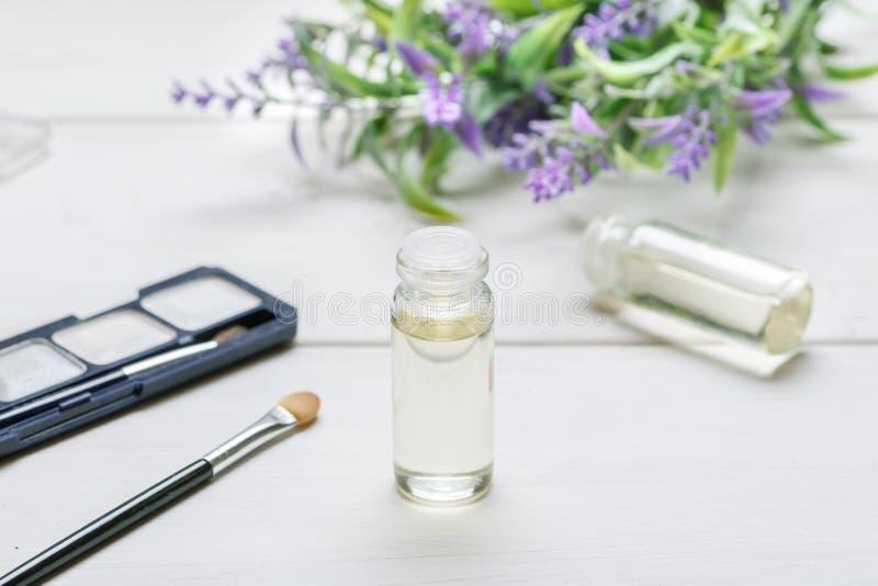Garrafa de vidro com óleo nele, em artigos cosméticos da composição e em flor da alfazema em uma tabela de madeira branca imagem de stock royalty free
