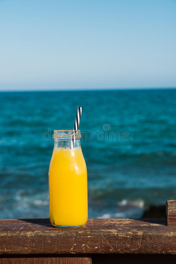 Garrafa de vidro com a tangerina alaranjada do suco dos citrinos com palha no trilho de madeira, no mar de turquesa e no céu azul fotos de stock