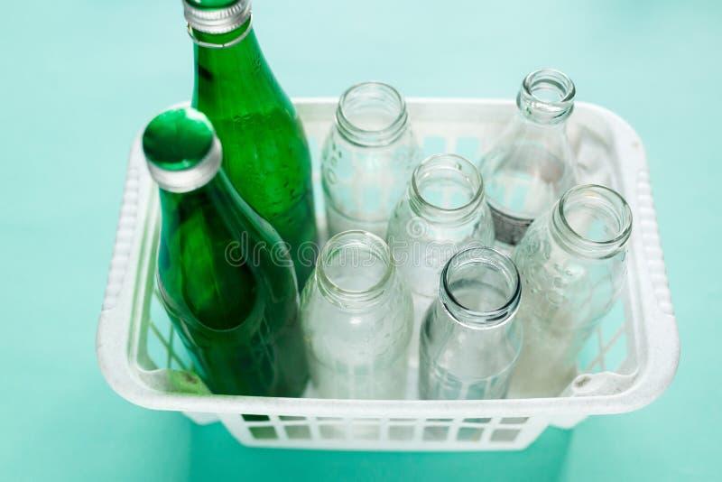 A garrafa de vidro diferente desperdiça pronto para reciclar na cesta branca no fundo verde Responsabilidade social, cuidado da e imagem de stock royalty free