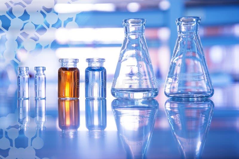 Garrafa de vidro e solução azul e alaranjada no tubo de ensaio para o laboratório da experiência da ciência médica e da educação  fotos de stock royalty free