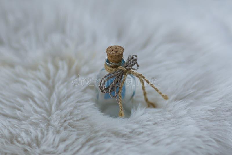 Garrafa de vidro pequena com tampa da cortiça no cargo branco fotos de stock royalty free