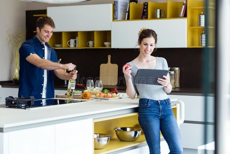 Garrafa de vinho considerável da abertura do homem novo quando sua esposa que usa a tabuleta digital na cozinha fotografia de stock royalty free