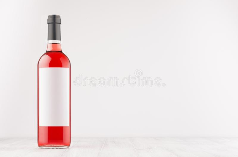 A garrafa de vinho de Rosa com etiqueta branca vazia na placa de madeira branca, zomba acima foto de stock