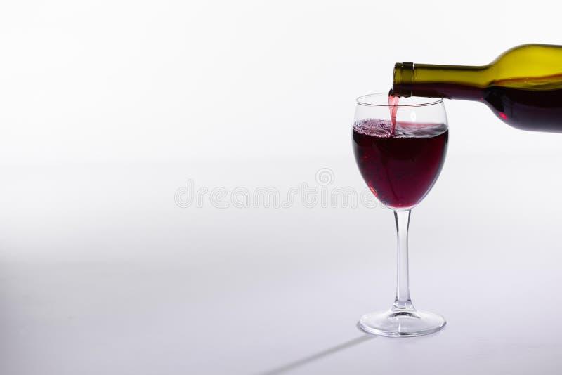A garrafa de vinho tinto derrama o vidro no fundo branco com espaço da cópia fotografia de stock royalty free