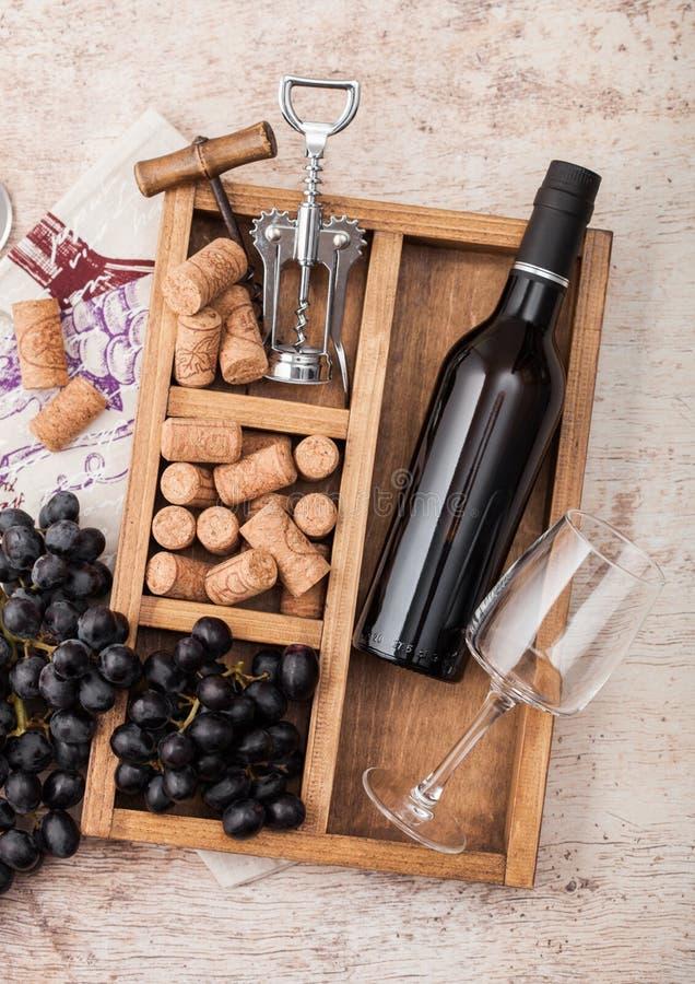 Garrafa de vinho tinto e de vidro vazio com uvas escuras, com rolhas e opener no interior de uma caixa de madeira de vintage sobr fotos de stock