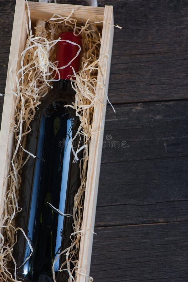 Garrafa de vinho tinto no caso de madeira com palha fotografia de stock