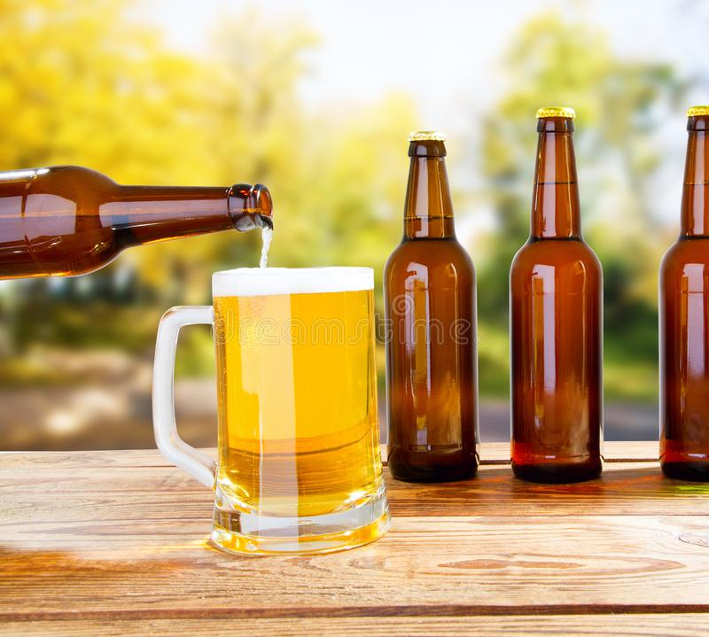 A garrafa derrama a cerveja no copo na tabela de madeira no fundo borrado do parque imagem de stock