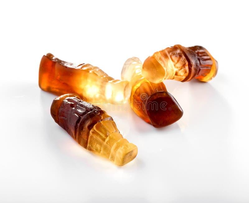 A garrafa deu forma a gummies com close-up do sabor da cola no fundo branco foto de stock royalty free
