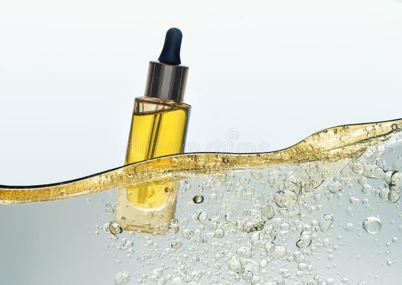 A garrafa do óleo cosmético amarelo na onda da emulsão do óleo imagem de stock royalty free