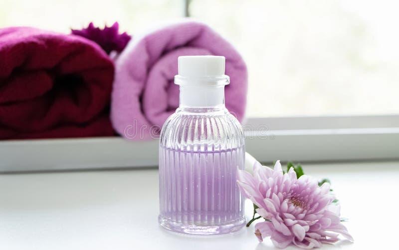 A garrafa do óleo da massagem posta ao lado da flor cor-de-rosa, aromatheraphy imagem de stock