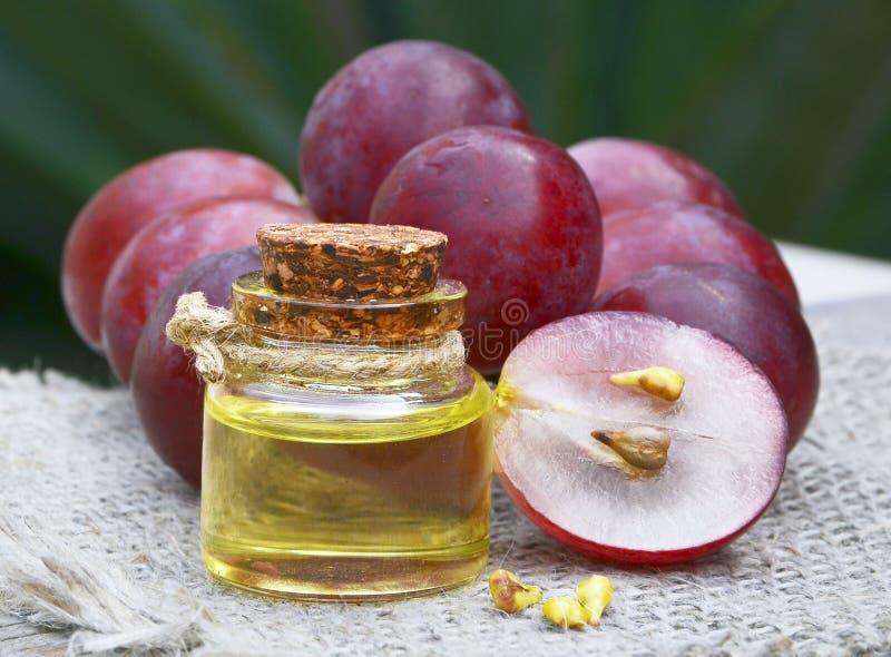 Garrafa do óleo de semente orgânico da uva para termas e bodycare e de bagas maduras frescas das uvas na tabela de madeira velha fotos de stock