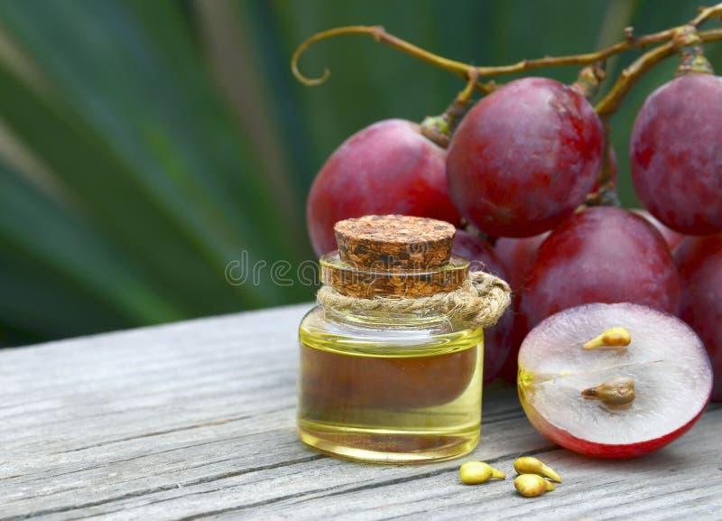 Garrafa do óleo de semente orgânico da uva para termas e bodycare e de bagas maduras frescas das uvas na tabela de madeira velha imagem de stock