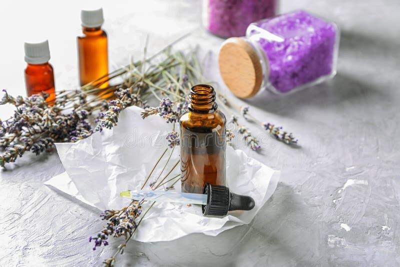 Garrafa do óleo essencial com alfazema na tabela fotos de stock