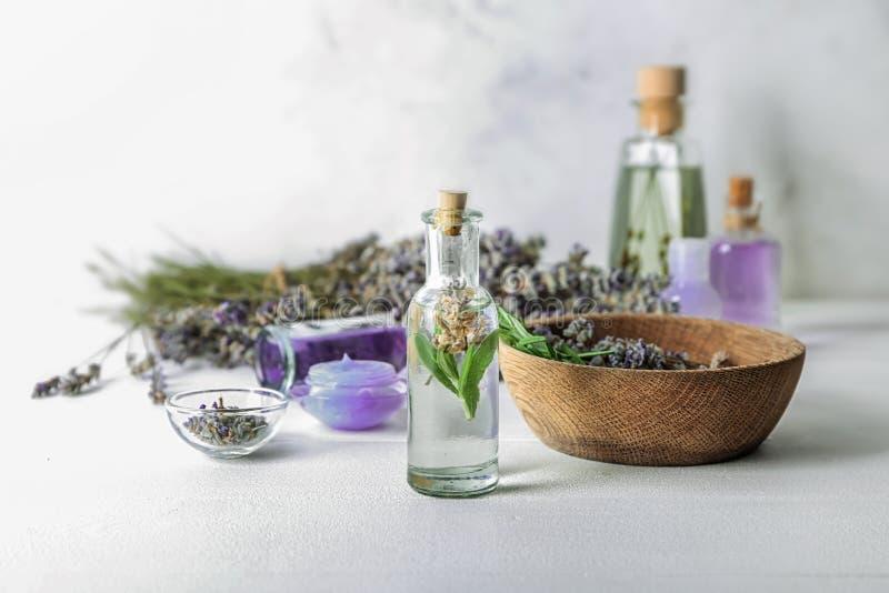 Garrafa do óleo essencial com alfazema na tabela clara fotografia de stock royalty free