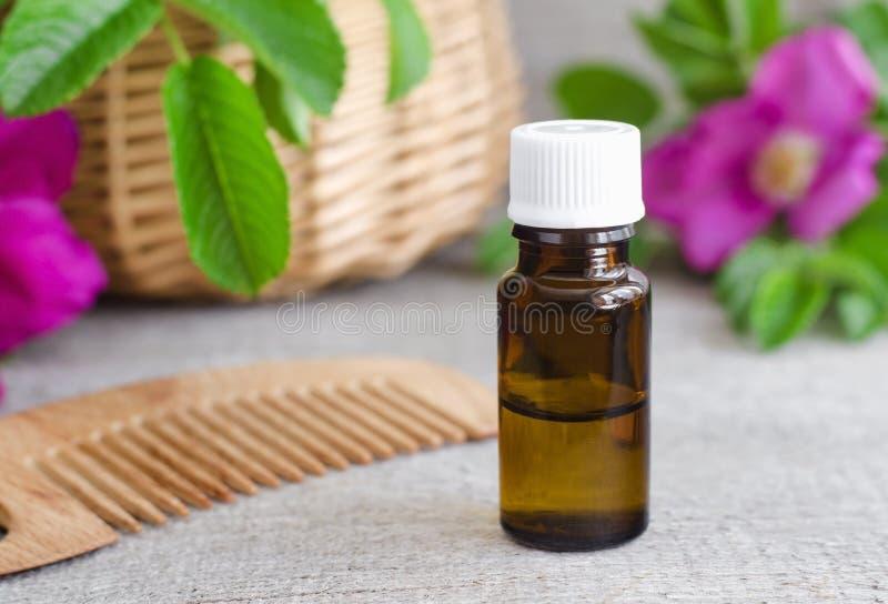 Garrafa do óleo (essencial) cosmético natural do aroma e do pente de madeira do cabelo imagem de stock
