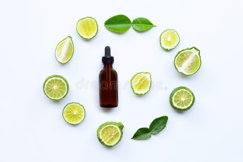 Garrafa do óleo essencial e do cal do kaffir ou do fruto fresco da bergamota com folhas foto de stock