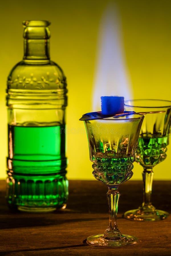 Garrafa do absinto e vidros com açúcar mascavado ardente do cubo fotografia de stock