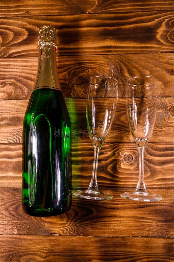 Garrafa do champanhe e dos dois copos de vinho na tabela de madeira a parte superior vie foto de stock