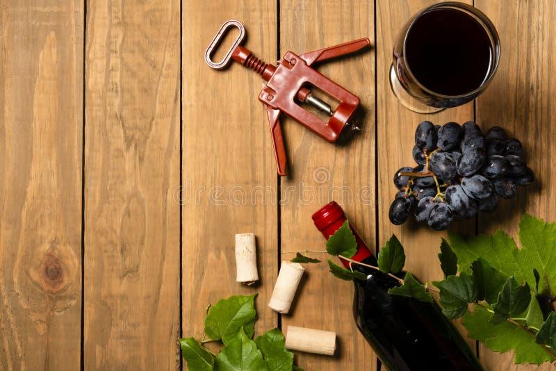 Garrafa do grupo do vinho de uvas e de bujão da cortiça no fundo de madeira Vista superior com espaço da cópia fotos de stock royalty free