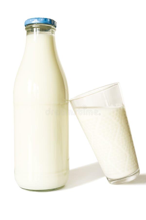 Garrafa do leite com o vidro azul da tampa e de leite - isolado no fundo branco imagens de stock